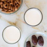 a close up of 2 cups of almond milk ready to drink surrounded by raw almonds and fresh medjool dates
