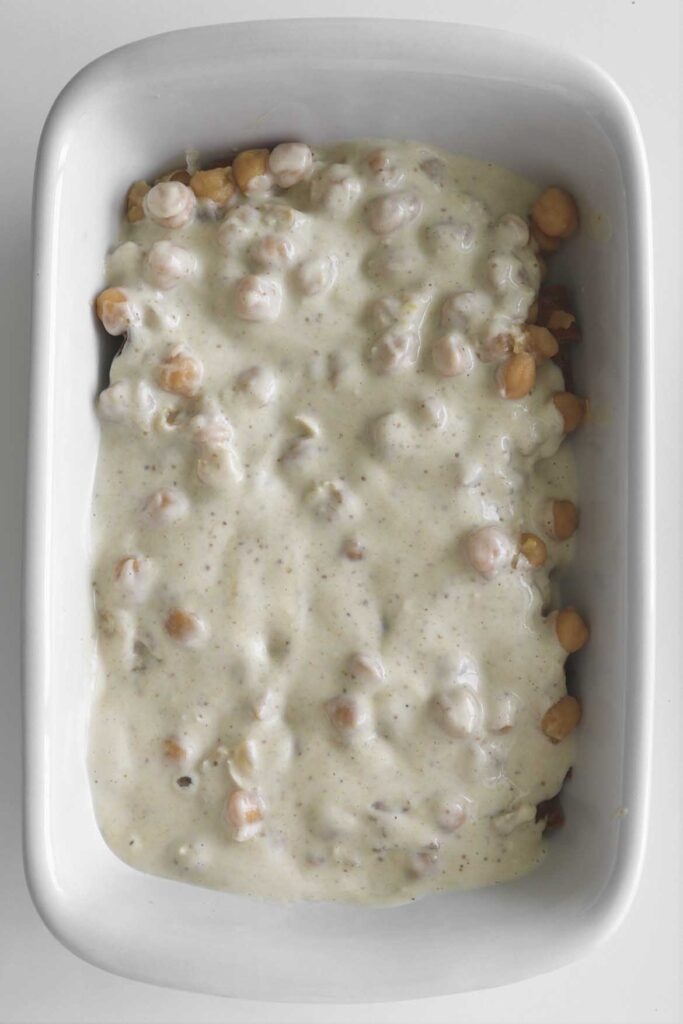 tahini yogurt layered on top of the chickpeas and toasted pita