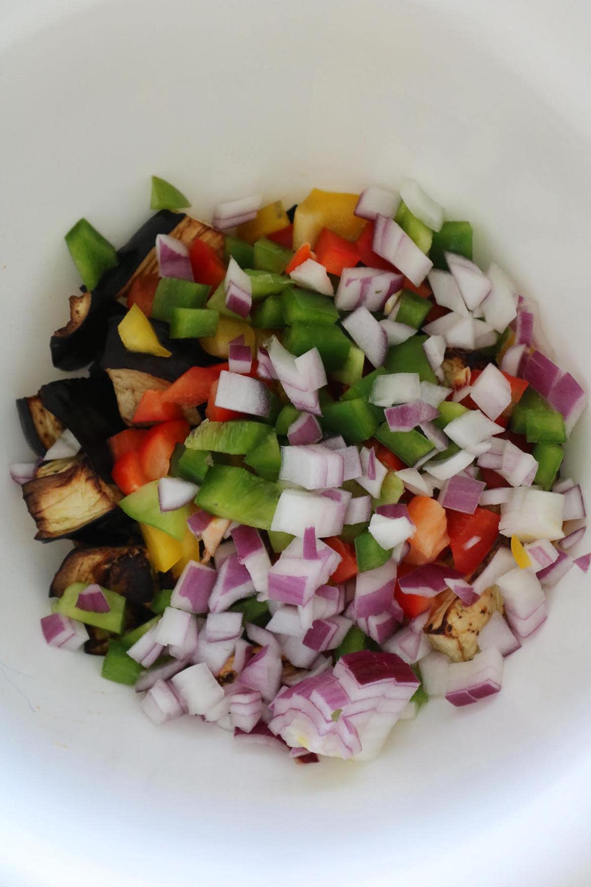 fried eggplant salad ingredients added to a bowl