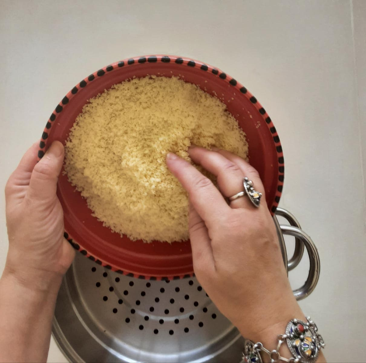 pouring couscous into a steamer tray