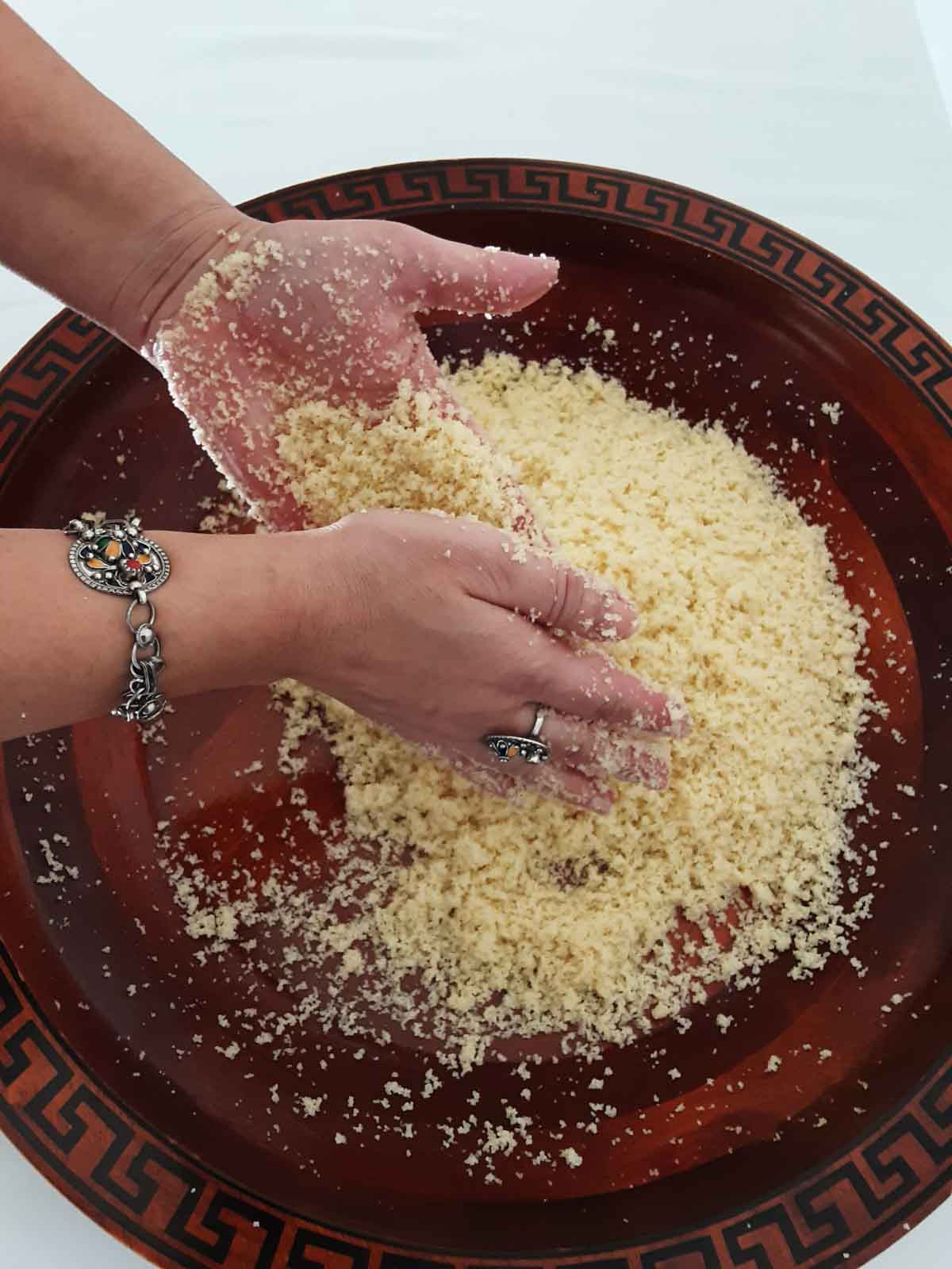 rubbing couscous between hands to separate out the grains