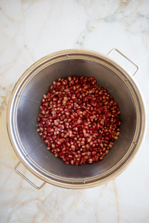 straining the pomegranate seeds using a strainer