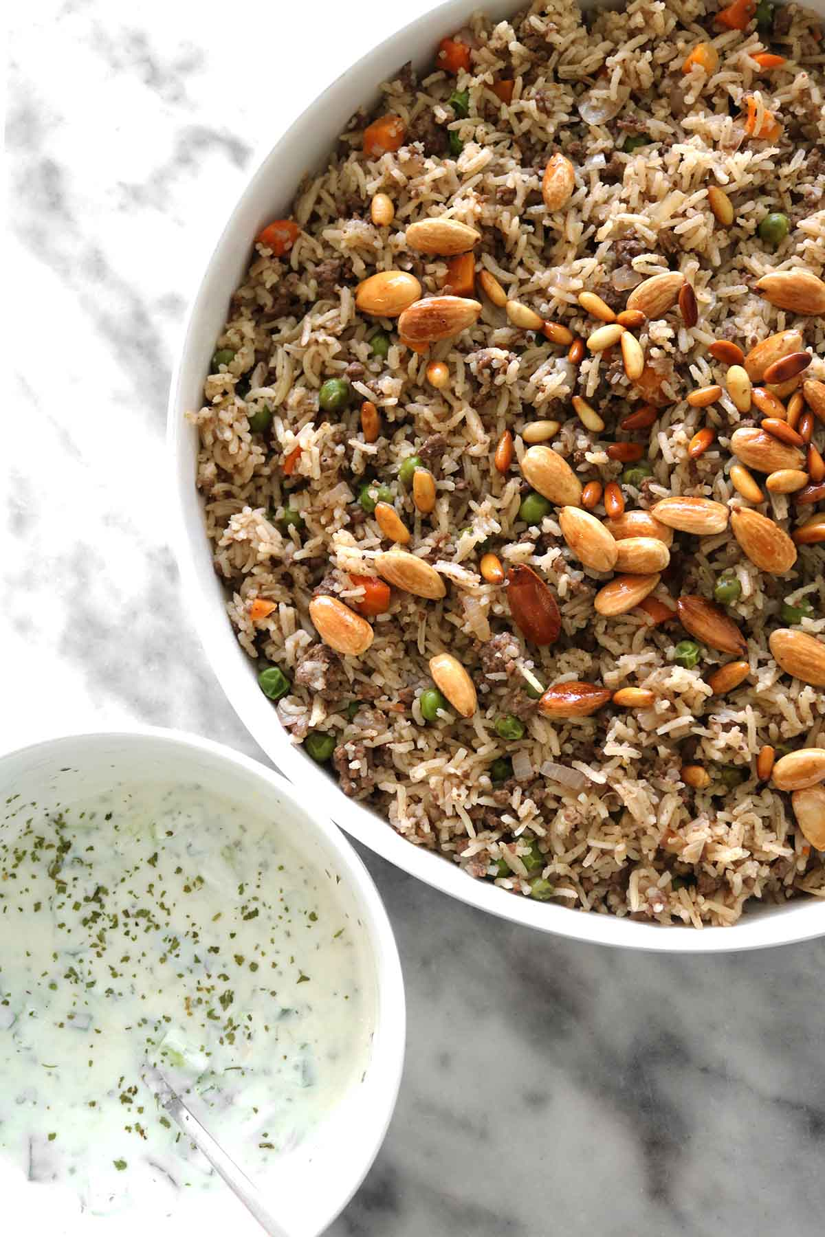 ouzi spiced rice with lamb in a bowl next to yogurt