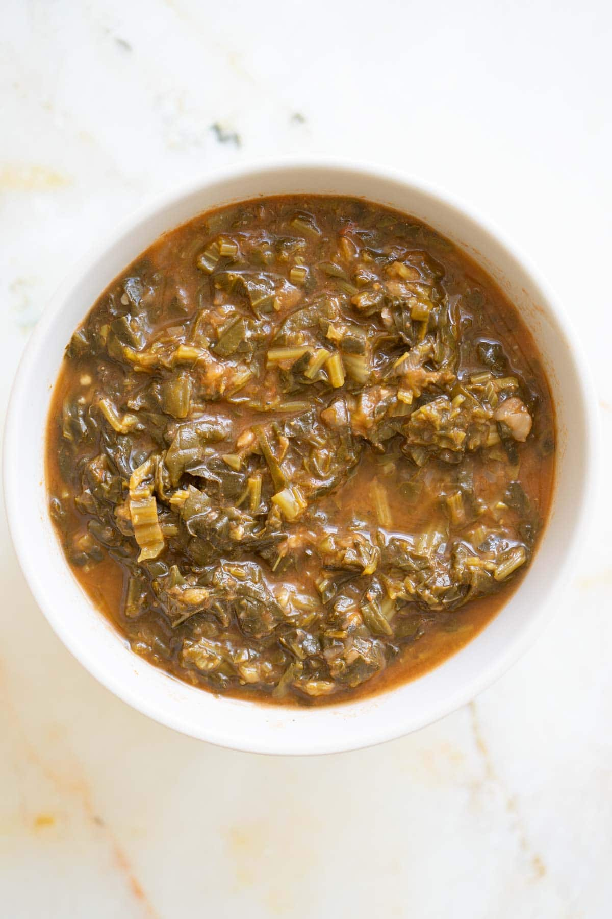 Egyptian sauteed spinach with tomato sauce in a bowl