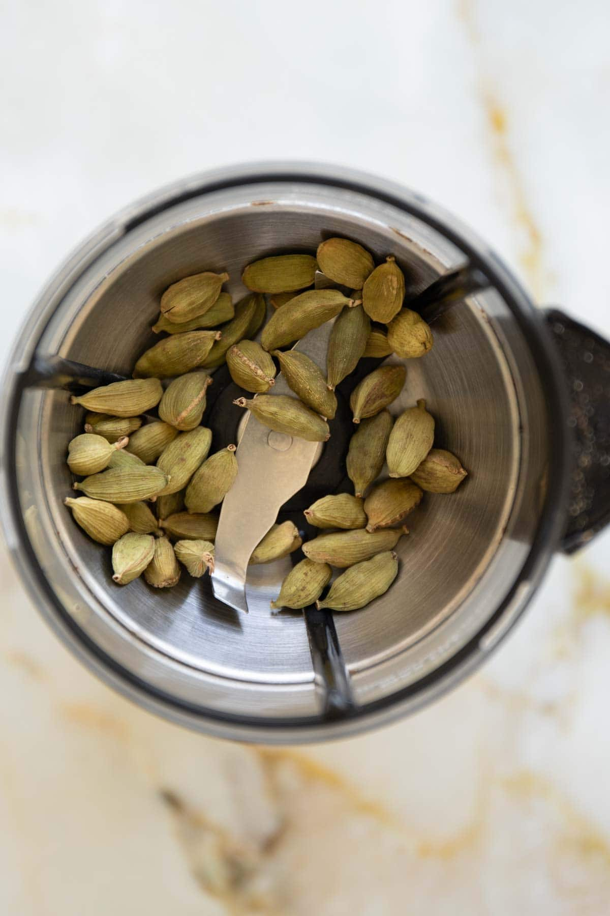 whole cardamom pods in a spice grinder