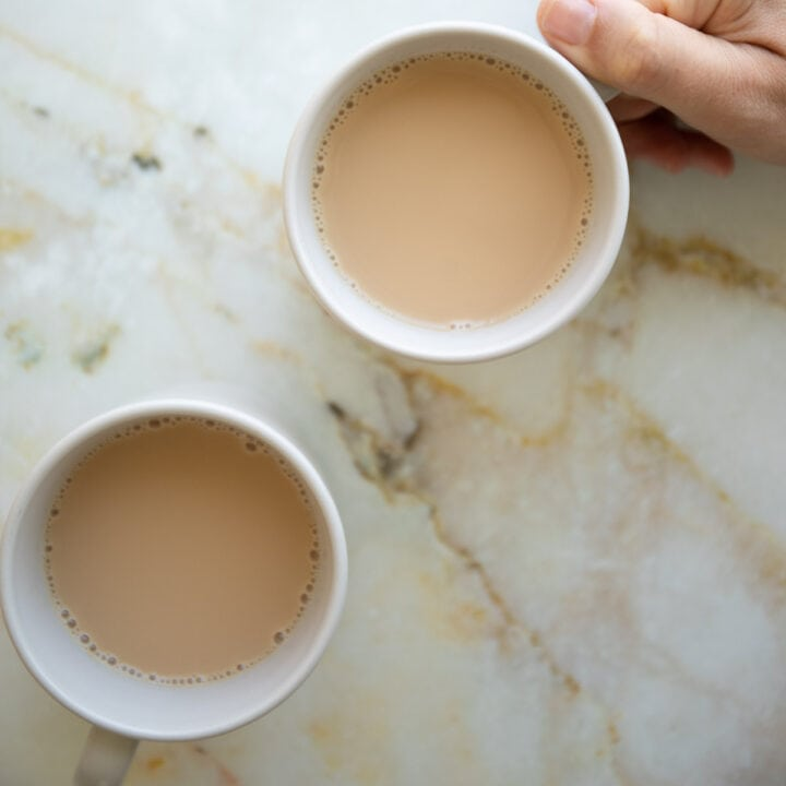 holding a cup of karak chai tea