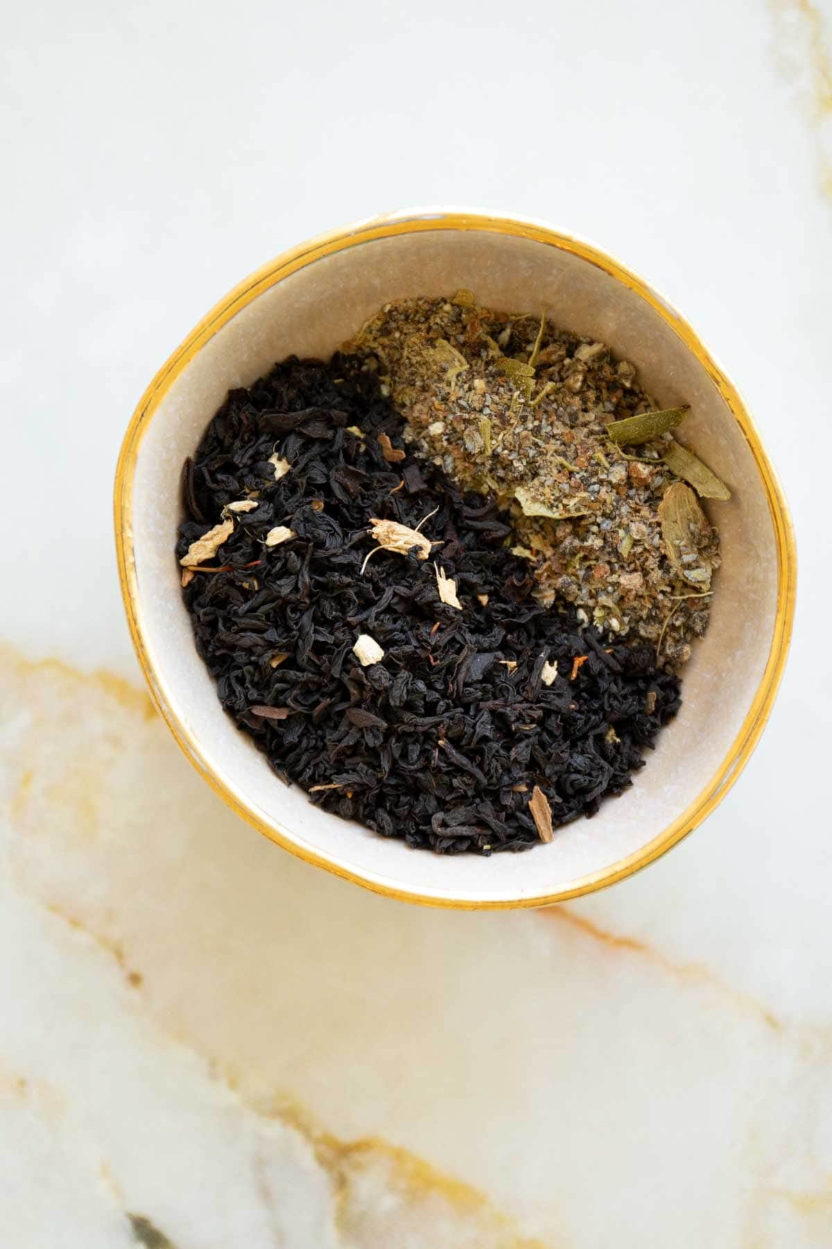 black tea with crushed cardamom in a bowl