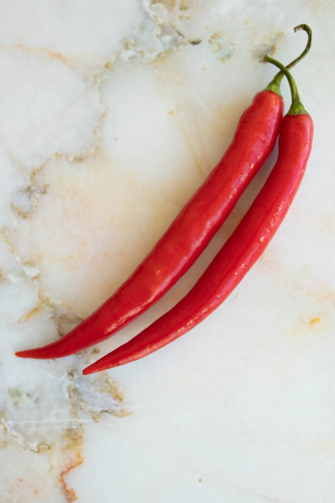 two red peppers on a countertop