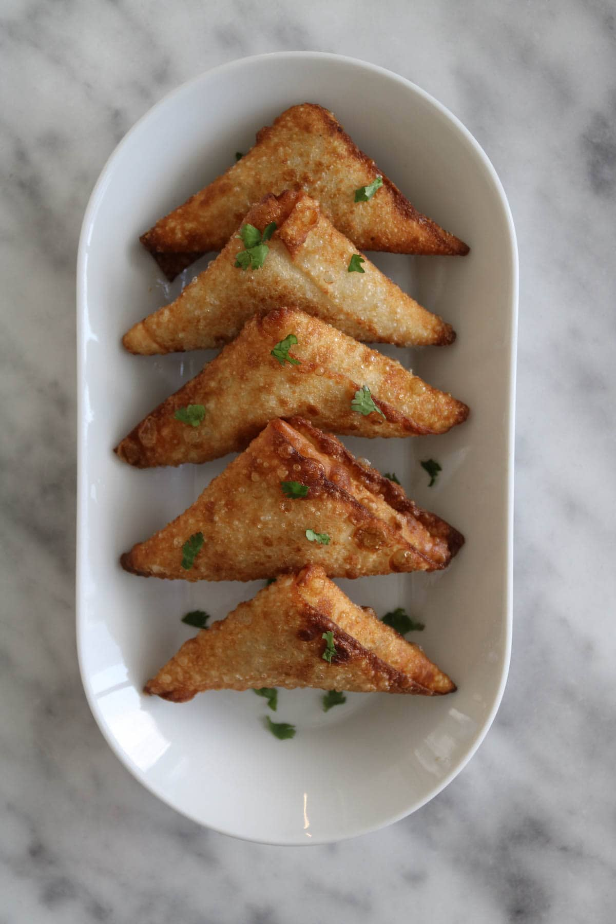 beef samosas lined up on a plate