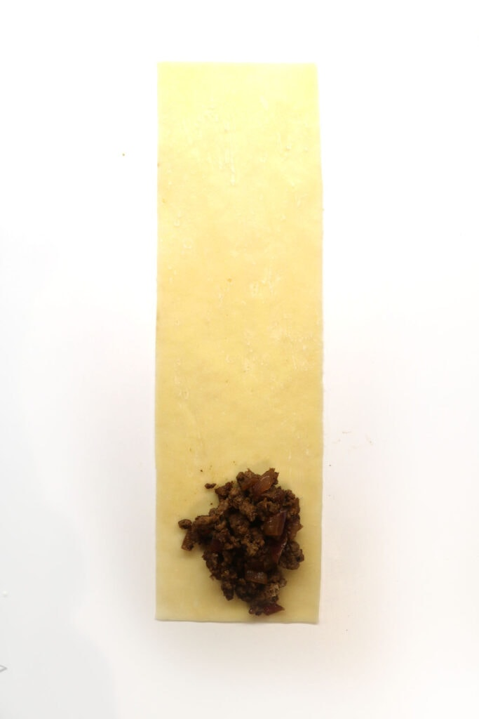 how to roll a samosa. Lay the samosa wrapper flat and place the minced meat mixture at the bottom of the wrapper