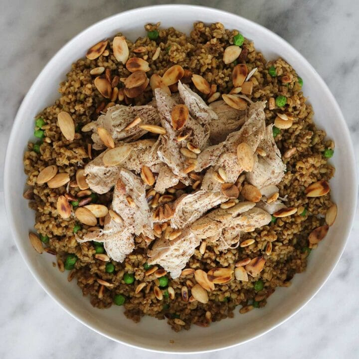 chicken freekeh with peas and nuts in a bowl