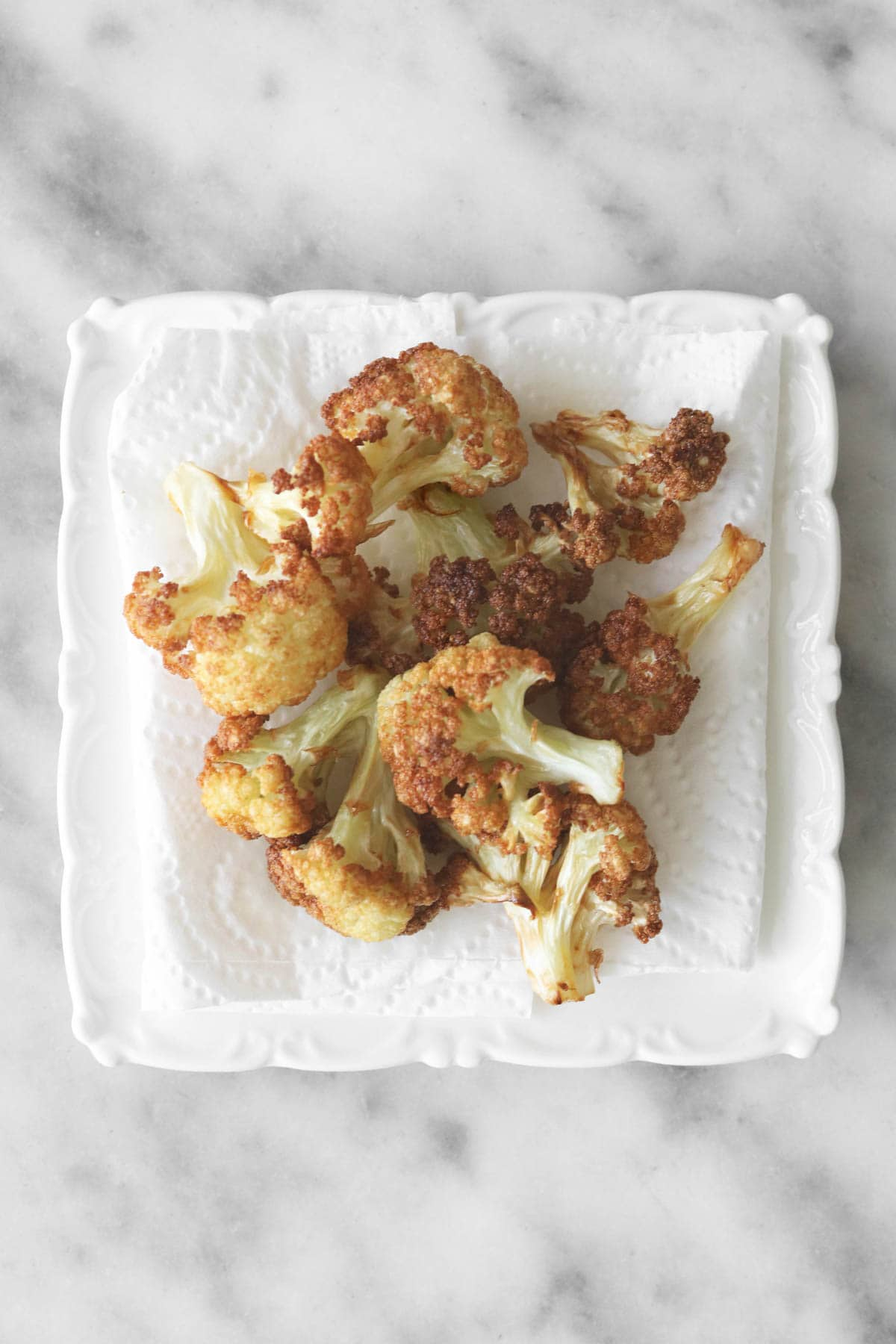 fried cauliflower florets on a paper towel