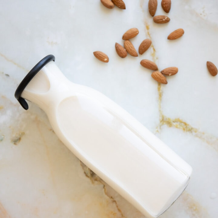 close up image of almond milk in a glass container