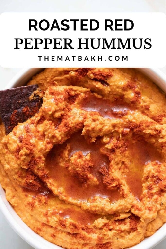 eating roasted red pepper hummus with a chip