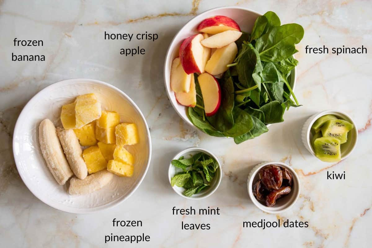 detox green smoothie with spinach ingredients laid out on a counter top