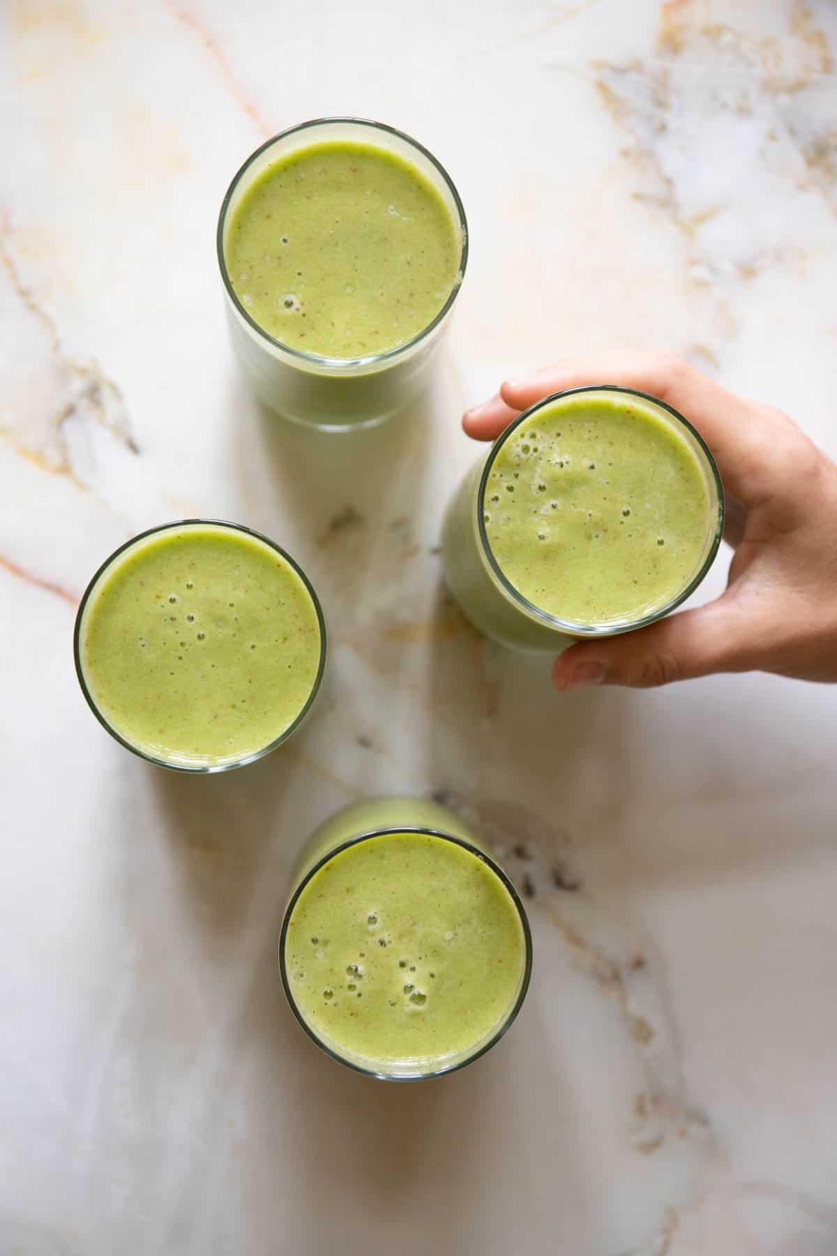 a person is grabbing a green smoothie drink