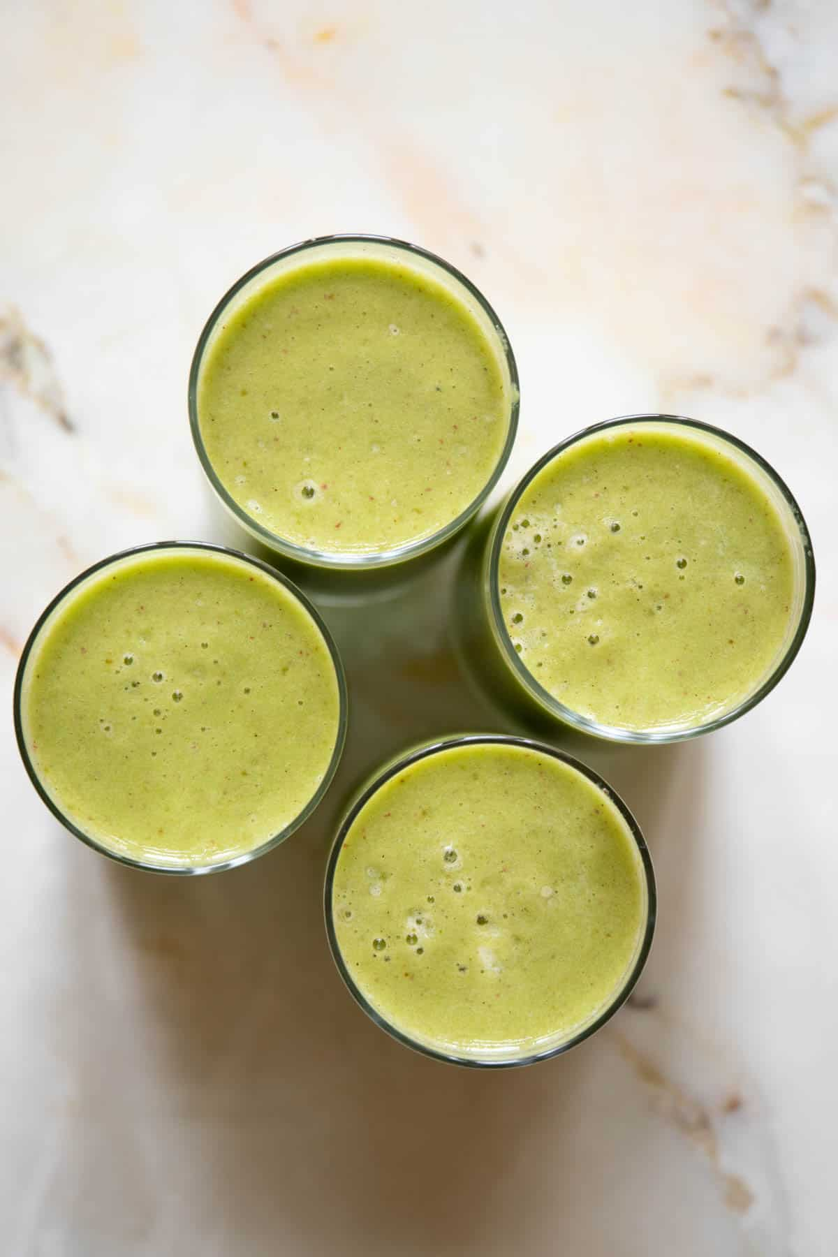 four glass cups of a green smoothie