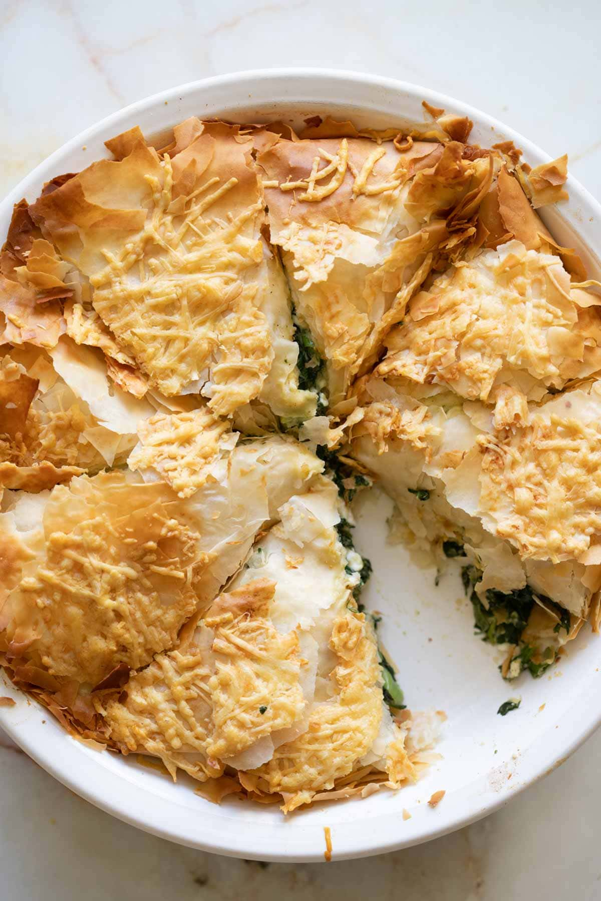 a piece cut out of the spanakopita pie