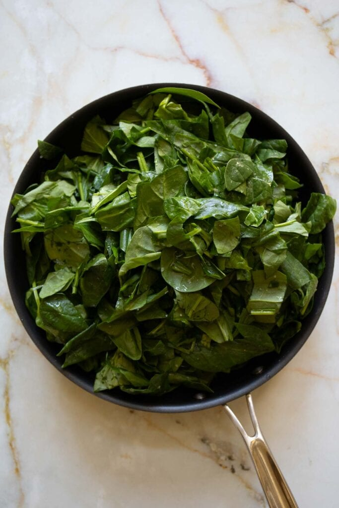 roughly chopped spinach in a pan
