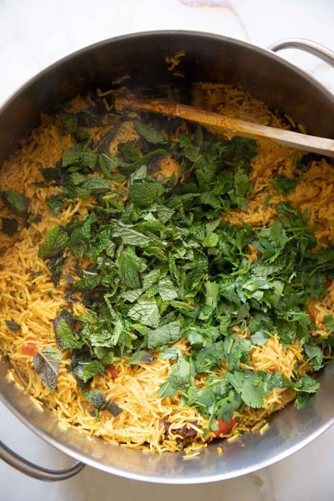 adding chopped cilantro and chopped mint to the biryani rice
