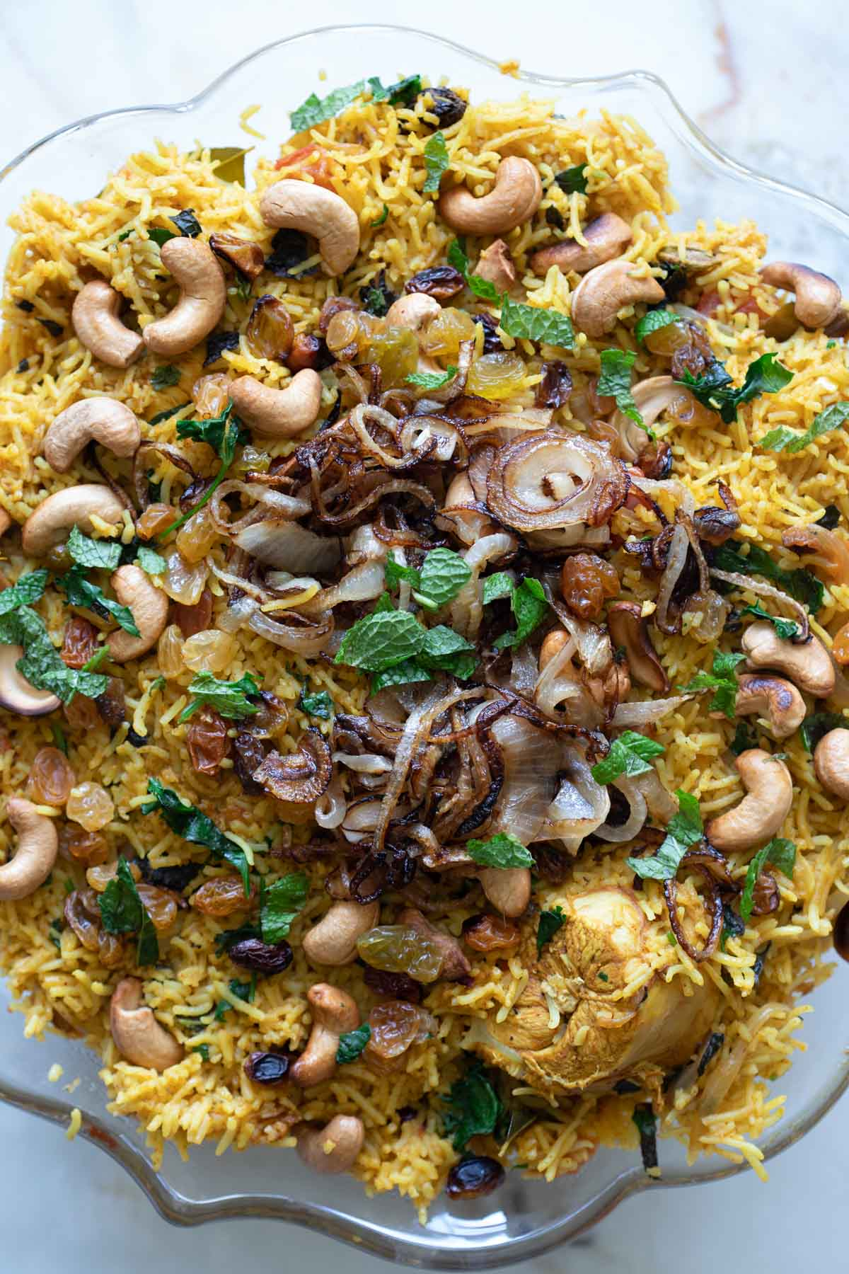 adding the toasted cashews, fried onions, and golden raisins to the chicken biryani rice