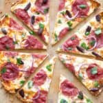 close up of pita bread salami pizza with onion and black olives