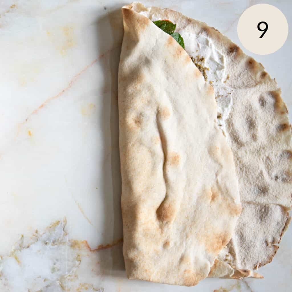 folding over the left side of the pita bread
