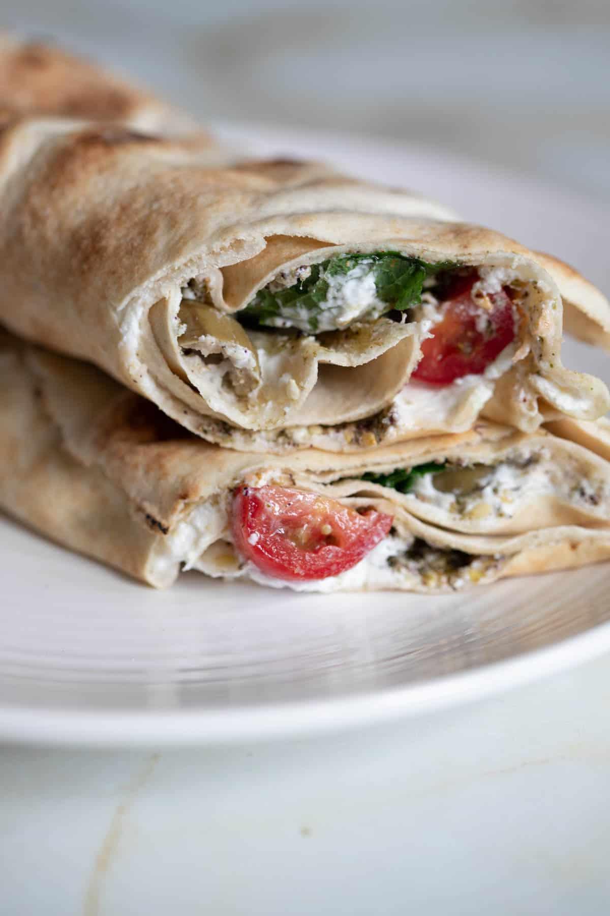 labneh pita sandwich on a plate cut in half