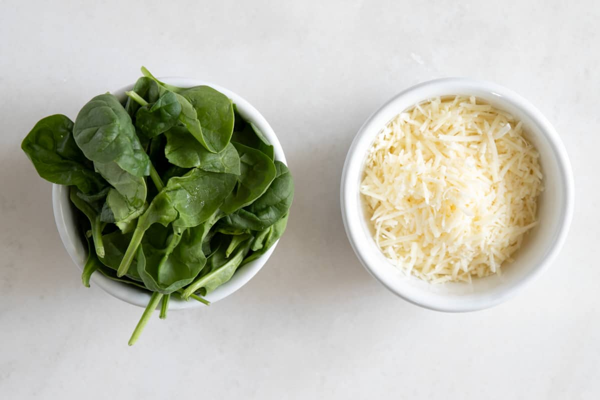 grated parmesan and fresh spinach in a bowl
