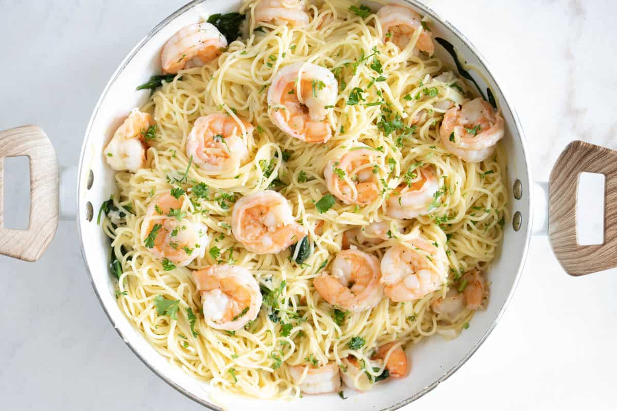 garlic lemon butter shrimp with angel hair pasta and spinach and parmesan in a pan