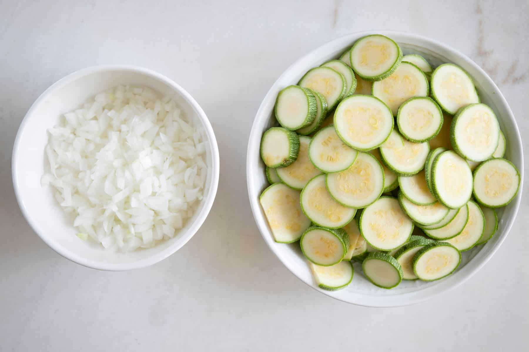 sliced kousa and chopped onions in a bowl