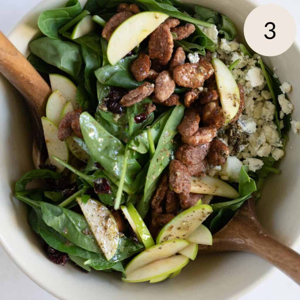 mixing the apple gorgonzola spinach salad with wooden salad spoons