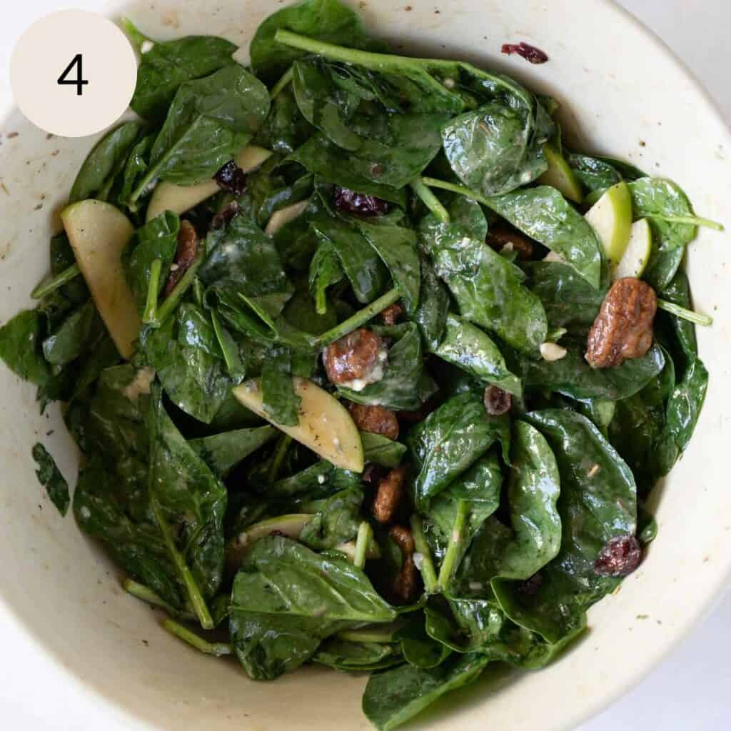 mixing the apple gorgonzola spinach salad with olive oil and vinegar salad dressing