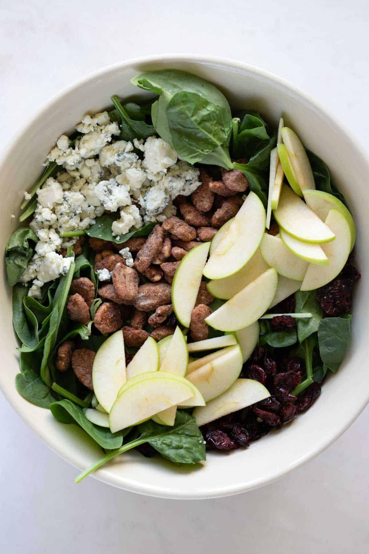 apple gorgonzola spinach salad in a bowl