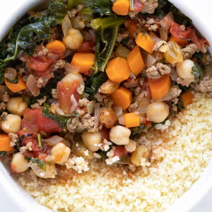harissa lamb chili with kale and couscous in a bowl