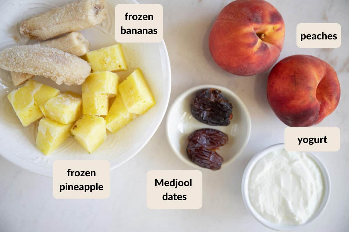 the ingredients needed to make a peach, banana, and pineapple smoothie