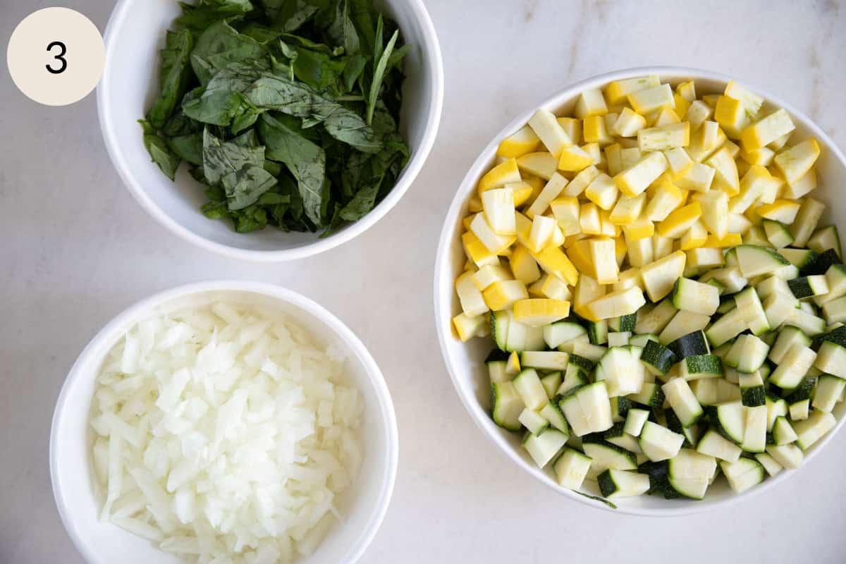 chopped zucchini, chopped squash, chopped onions, and chopped basil in bowls