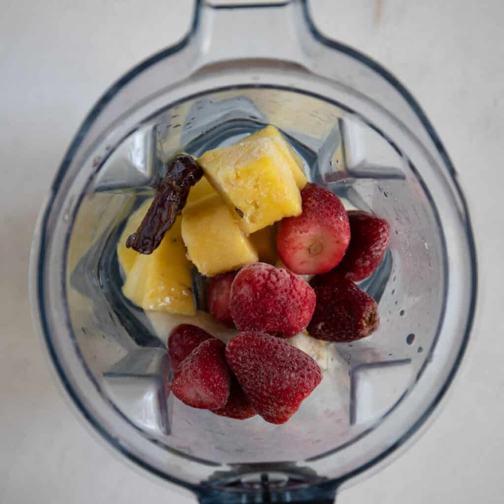 add the frozen strawberries, frozen banana, pineapple, and Medjool date to blender with water