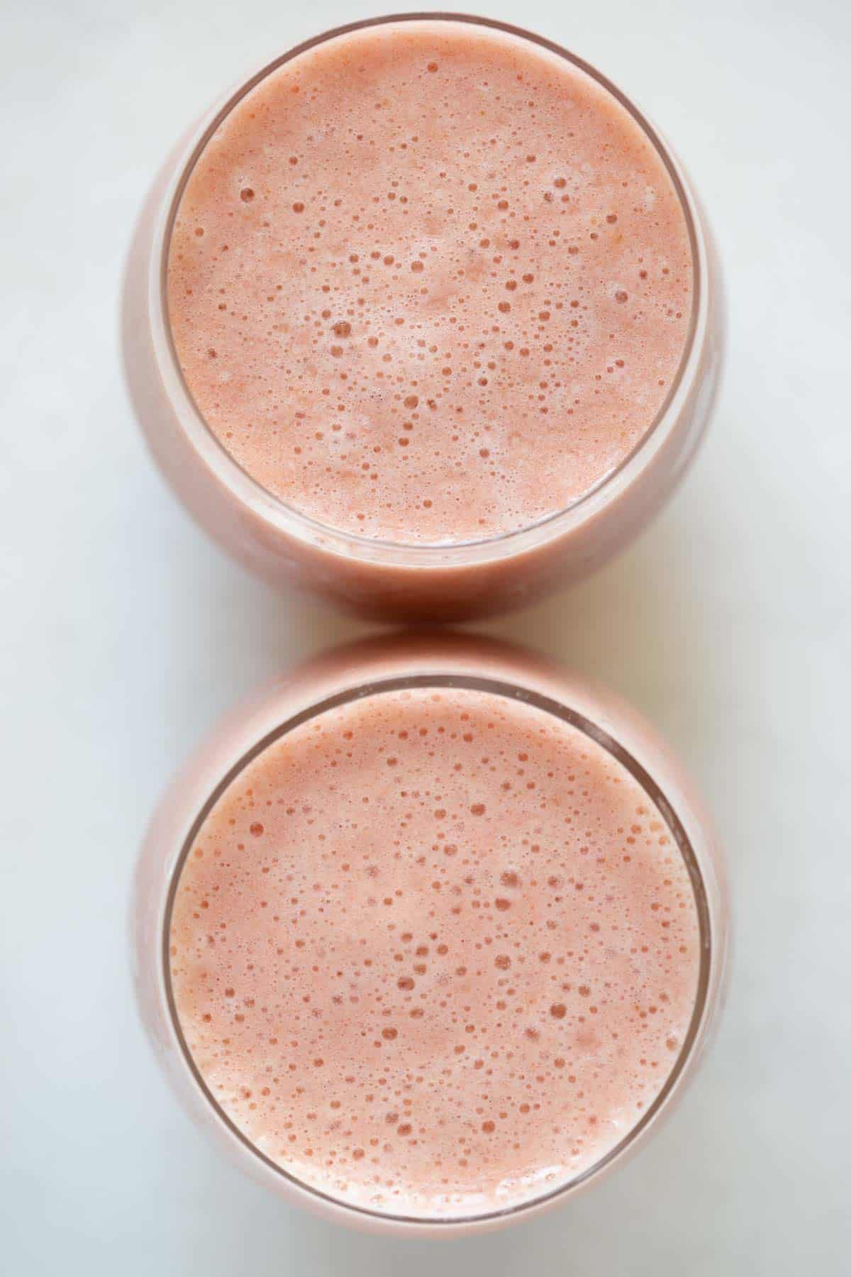 strawberry banana pineapple smoothie in two glass cups