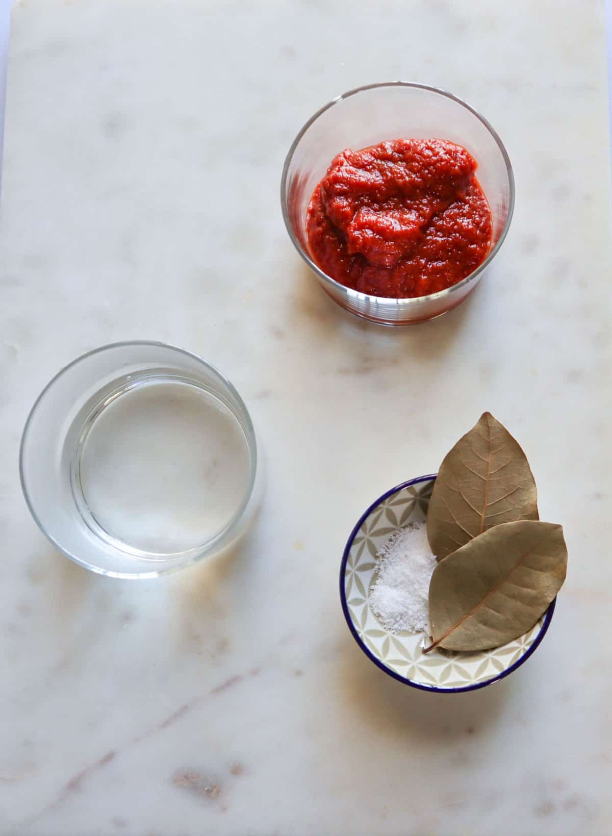 tomato paste, salt, and bay leaves