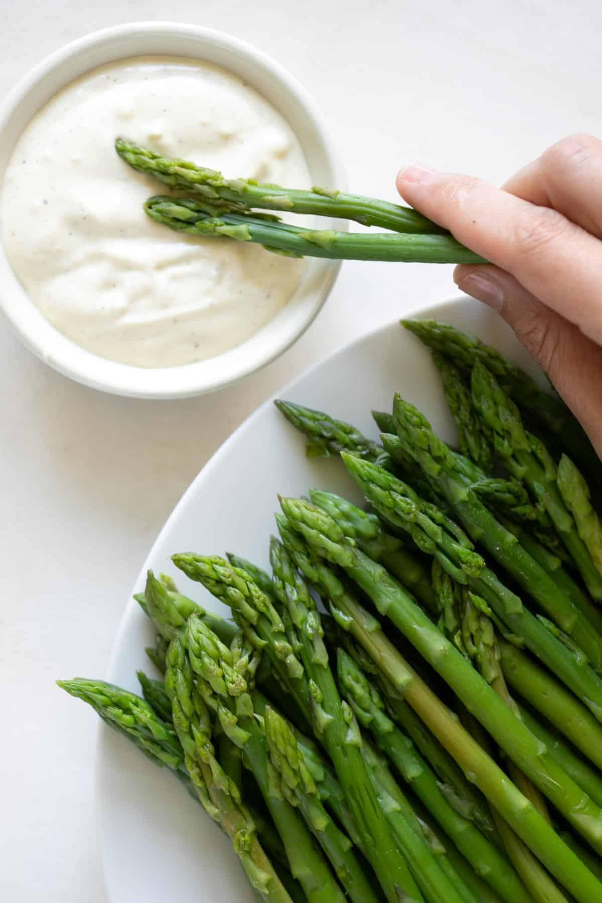 dipping blanched asparagus in lemon garlic aioli