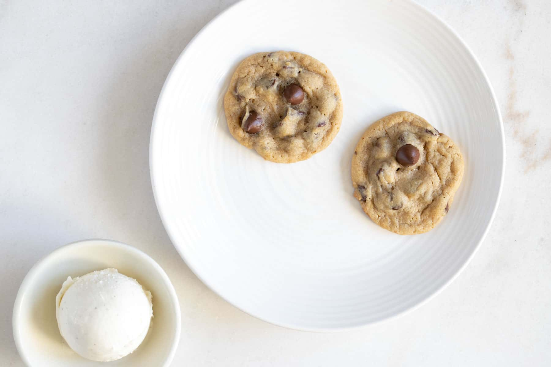 two chocolate chip cookies on a plate with a scoop of ice cream in a bowl