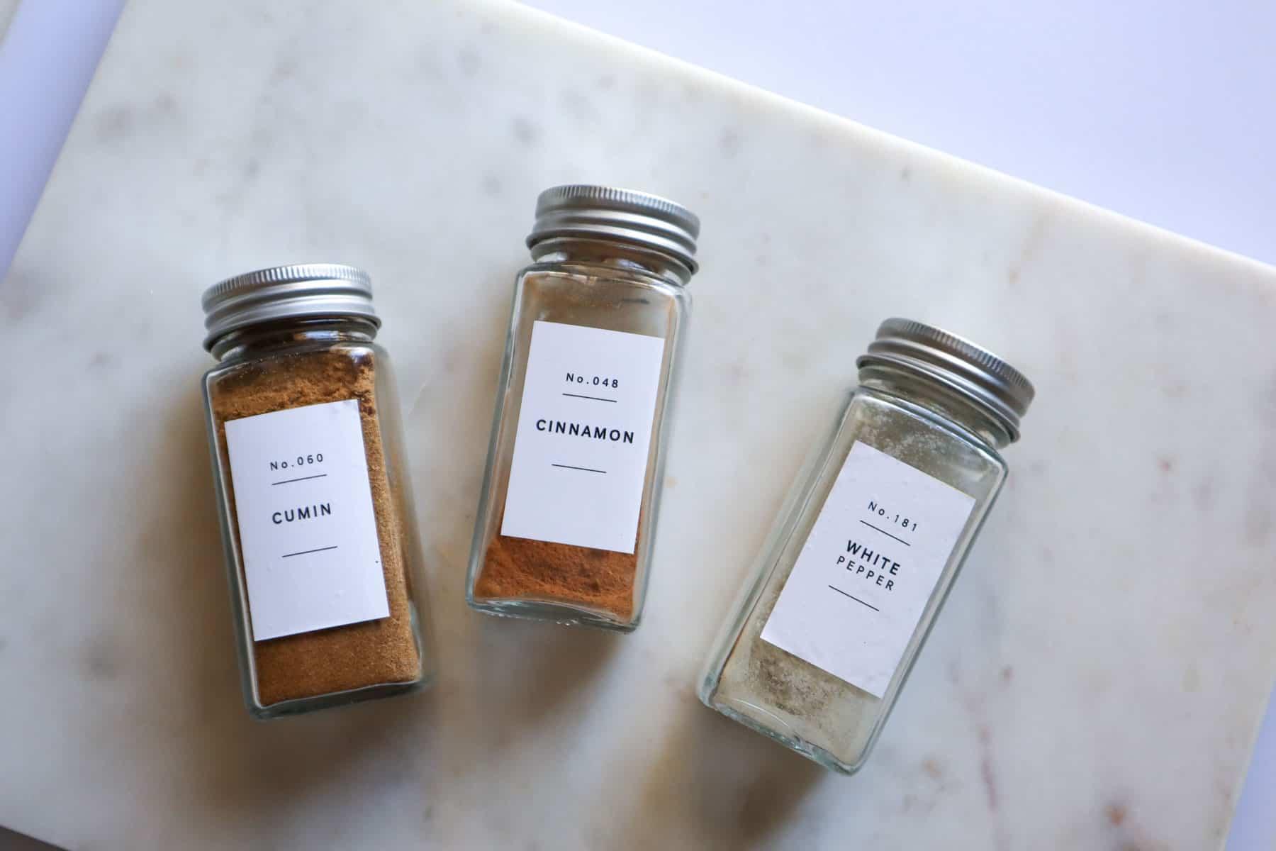 ground cumin, ground cinnamon, and ground white pepper in separate spice jars