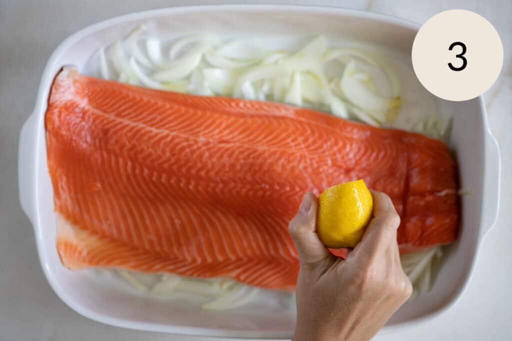 squeezing lemon on the steelhead trout fish