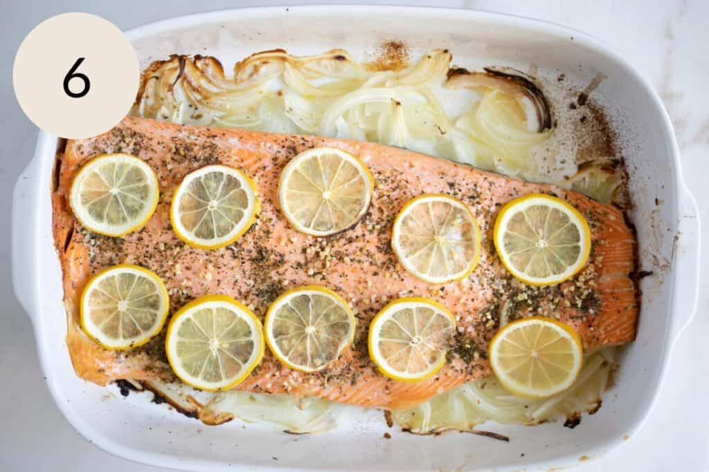 the trout fish after it's been baked in the oven over a bed of sliced onions